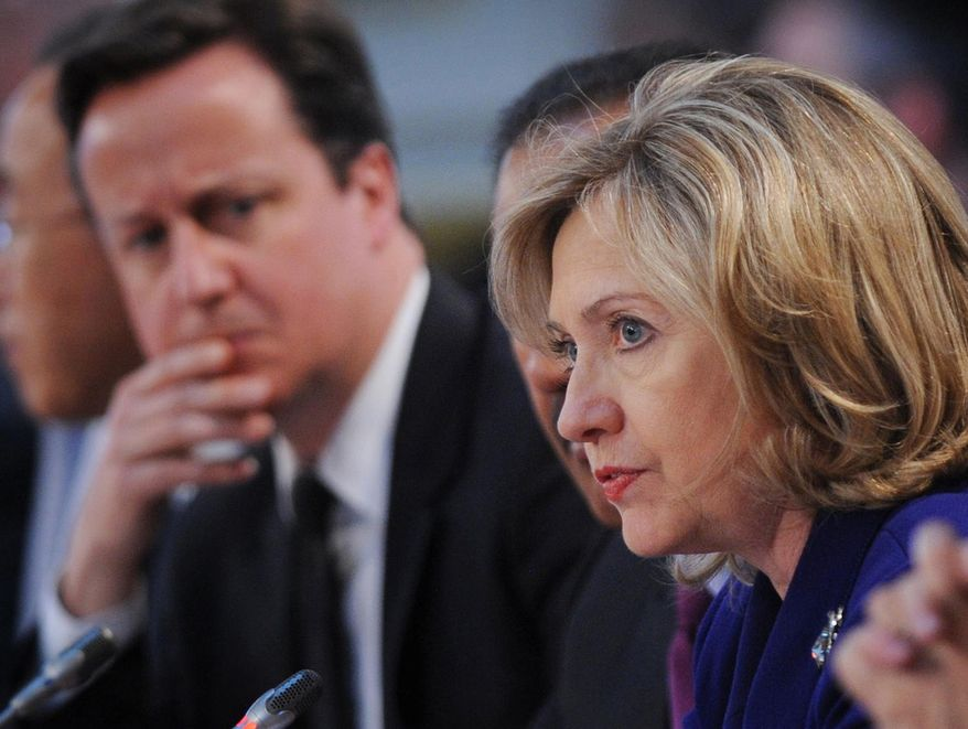 British Prime Minister David Cameron (left) listens as U.S. Secretary of State Hillary Rodham Clinton speaks at the London Conference on Libya on Tuesday, March 29, 2011. U.N. Secretary-General Ban Ki-moon, the Arab League, NATO chief Anders Fogh Rasmussen and up to 40 foreign ministers were attending the talks, seeking to ratchet up the pressure on Col. Moammar Gadhafi to quit. (AP Photo/Stefan Rousseau, pool)