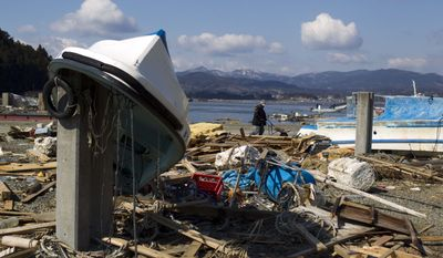 A resident of Japan's Oshima island pushes a wheelbarrow past the destroyed port as he tries to salvage belongings from his home on Monday, March 28, 2011, following the March 11 earthquake and tsunami. (AP Photo/David Guttenfelder)