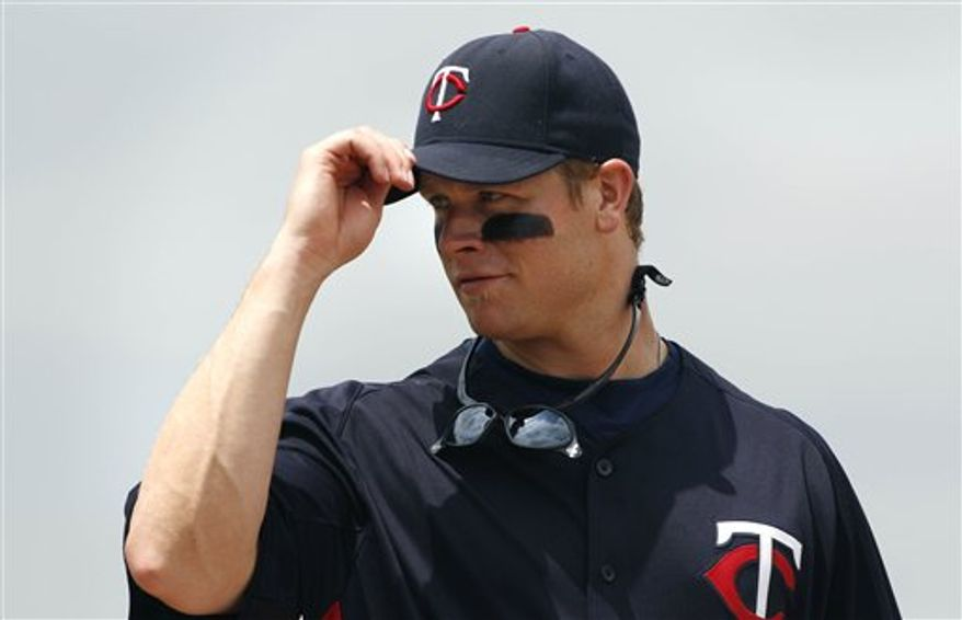 Minnesota Twins first baseman Justin Morneau tips his cap as he looks into the Pittsburgh Pirates dugout during the second inning of a spring training baseball game in Fort Myers, Fla., Monday, March 28, 2011. (AP Photo/Charles Krupa)
