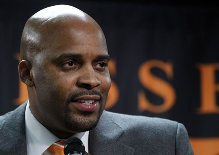 Cuonzo Martin speaks to reporters during a news conference as athletic director Mike Hamilton, left, listens, Monday, March 28, 2011, in Knoxville, Tenn., after Martin was named the new men's head basketball coach at the University of Tennessee replacing Bruce Pearl. Martin was head coach at Missouri State, an assistant at Purdue and a college basketball player. (AP Photo/Wade Payne)