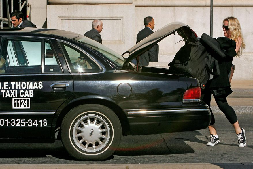 A passenger piles her bags into a cab after waiting in the taxi line at Union Station. Under a proposed medallion system, a government agency would issue cab owners the medallions, which are affixed to the cabs as proof that they are licensed and allow them to pick up passengers. (Associated Press)
