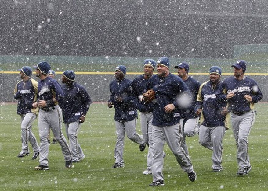 Milwaukee Brewers players jog in the snow at Great American Ball Park, Wednesday, March 30, 2011 in Cincinnati. The Brewers open their 2011 major league baseball season Thursday against the Cincinnati Reds in Cincinnati. (AP Photo/Al Behrman)