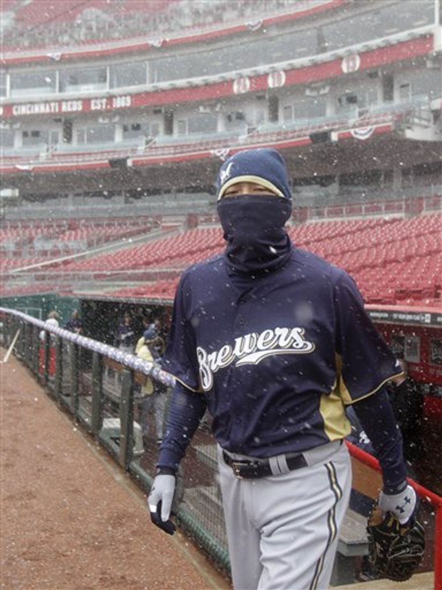Milwaukee Brewers relief pitcher Takashi Saito, from Japan, walks onto the field for a light workout in the snow, Wednesday, March 30, 2011 in Cincinnati. The Brewers open their 2011 major league baseball season Thursday against the Cincinnati Reds in Cincinnati.(AP Photo/Al Behrman)