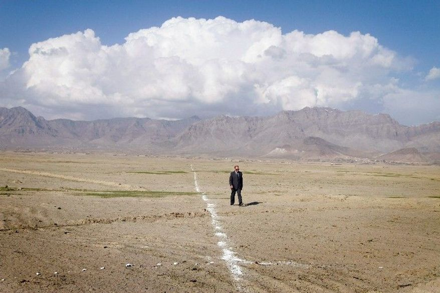 Elham Omar Hotaki, who works with the agency developing modern New Kabul City north of the war-torn capital, walks along an outline of its boundaries. (Associated Press)