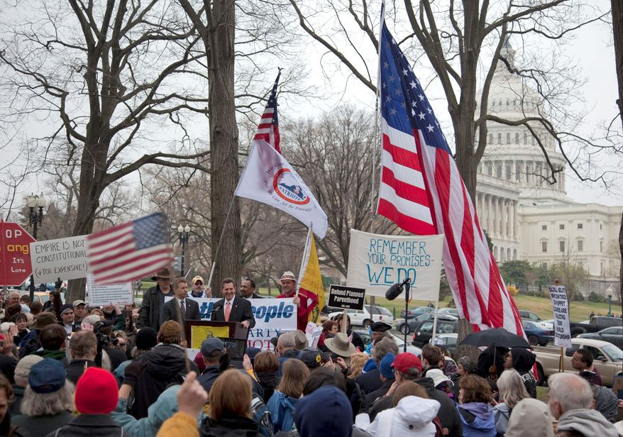 """Sen. Jim DeMint of South Carolina, with a fellow Republican, Sen. Rand Paul of Kentucky, to his right, addresses a tea party """"Continuing Revolution? rally Thursday on Capitol Hill. (Associated Press)"""