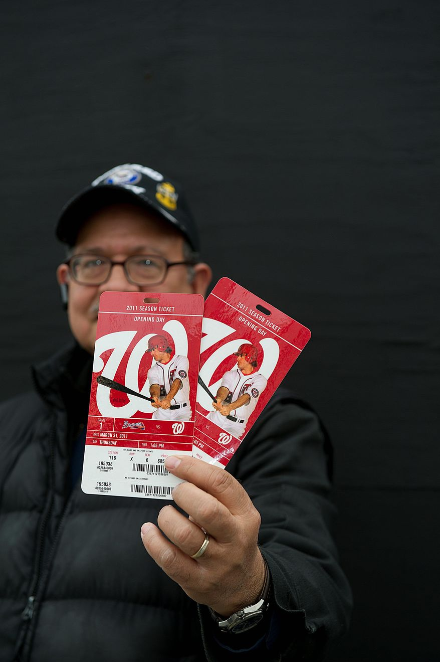 Julio Melendez of Arlington holds up two of his company's season tickets for the opener of the Nationals against the Atlanta Braves, which was dampened by occasional drizzle. (Barbara L. Salisbury/The Washington Times)