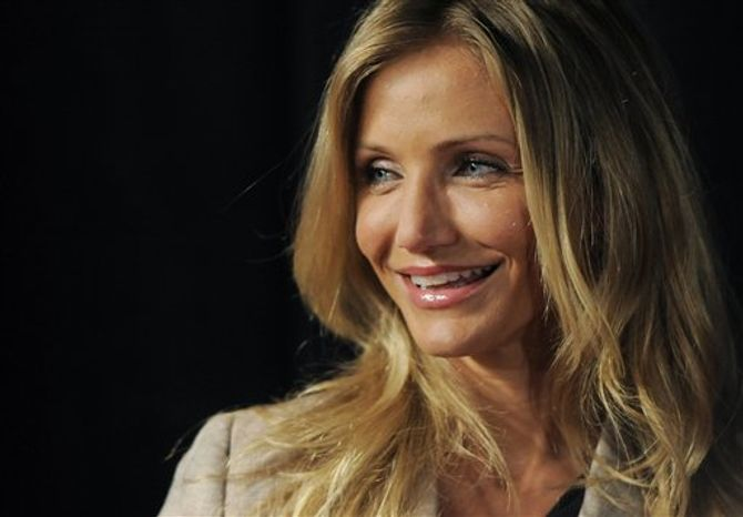 """Actress Cameron Diaz, recipient of CinemaCon's Female Star of the Year award, poses in front of a poster for her upcoming film """"Bad Teacher"""" at CinemaCon 2011 on Wednesday, March 30, 2011, in Las Vegas. (AP Photo/Chris Pizzello)"""