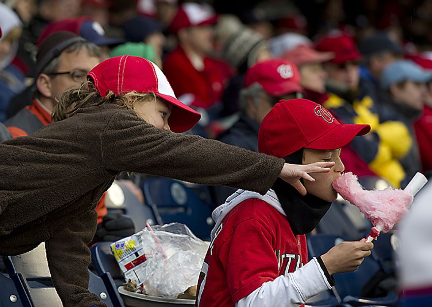 Lillian Matthews, 8, of Rockville, Md., reaches for her 10-year-old brother Carter's cotton candy during the Nationals opening day game Thursday, March 31, 2011 at Nationals Park in Washington, D.C. (Barbara L. Salisbury/The Washington Times)