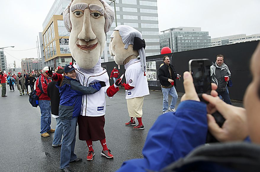 Angela Inguillo poses with one of the presidential mascots while her husband Michael takes the photo outside of Nationals Park as the Washington Nationals host the Atlanta Braves on Opening Day at Nationals Park in Washington, D.C., Thursday, March 31, 2011. (Rod Lamkey Jr/The Washington Times)