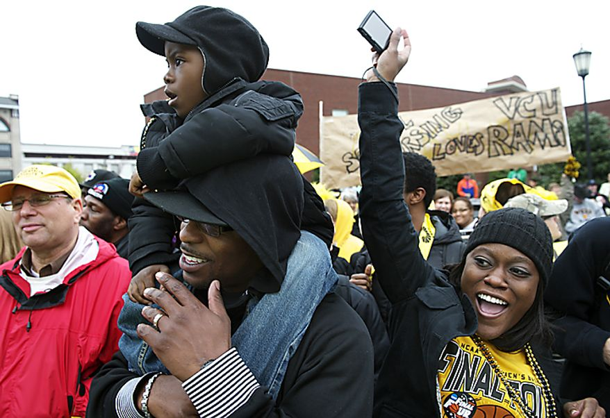 Virginia Commonwealth University alumnus James Carter carries his 6-year-old son, Thomas, on his shoulder while his wife, Enjoli, cheers as the crowd waits to watch the VCU men's basketball team depart from the campus in Richmond on Wednesday, March 30, 2011, en route to Houston for the school's first appearance in an NCAA Final Four tournament. (Rod Lamkey Jr./The Washington Times)