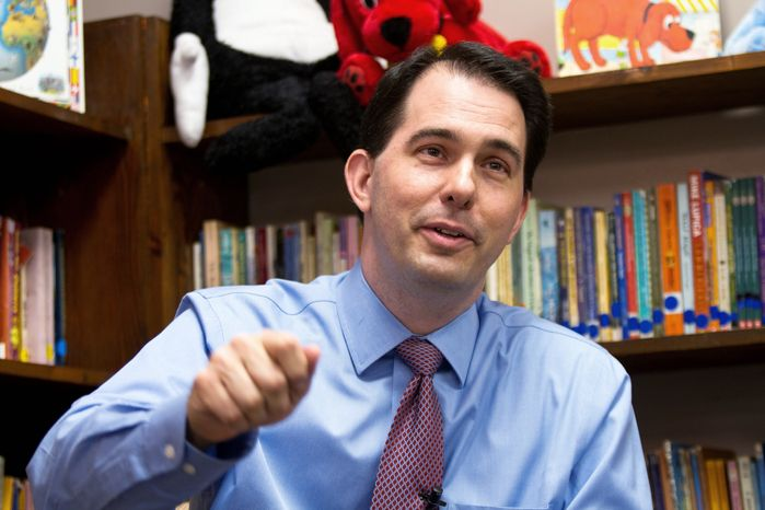**FILE** Republican Wisconsin Gov. Scott Walker answers news media questions March 31 after a circuit judge forced him to halt implementing a law that cripples collective bargaining. (Associated Press)