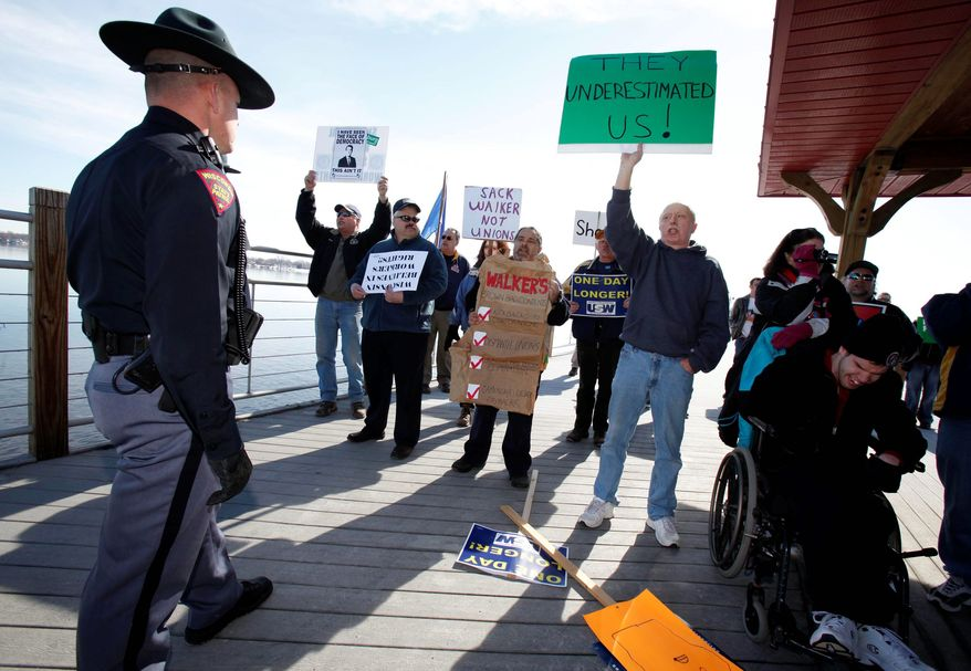 A Wisconsin State Patrol officer monitors protesters during Gov. Scott Walker's appearance in Menasha, Wis. Protests continue against the governor's budget plan. He wants to implement a law that would strip most public workers of their collective bargaining rights and cut their pay. (Associated Press)