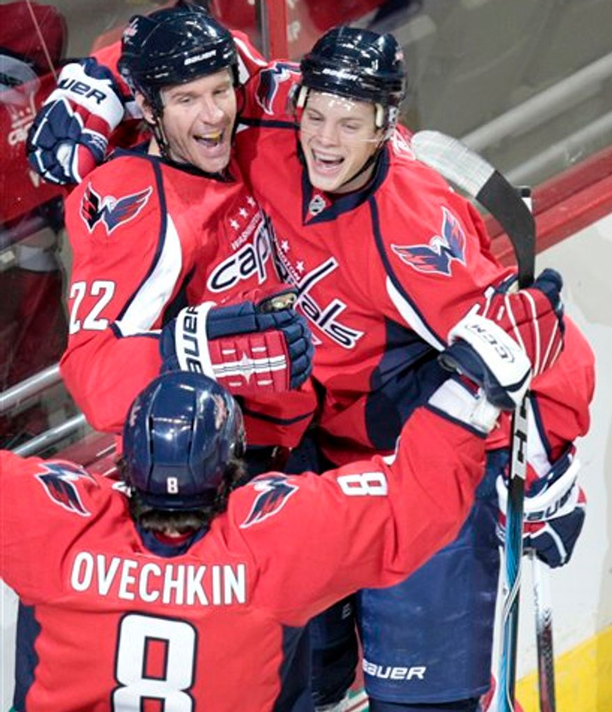 Washington Capitals' Mike Knuble (22) celebrates with teammates John Carlson, right, and Alex Ovechkin (8), of Russia, after scoring a goal against the Buffalo Sabres during the first period of an NHL hockey game Saturday, April 2, 2001, in Washington. The Capitals won 5-4 in overtime.(AP Photo/Luis M. Alvarez)