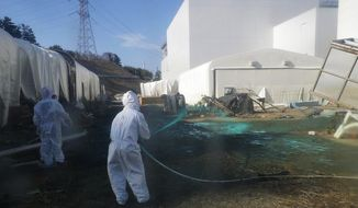 In this Friday, April 1, 2011, photo released by Tokyo Electric Power Co., workers for the company experimentally spray adhesive synthetic resin over the ground at the Fukushima Dai-ichi nuclear power plant in Okumamachi, northeastern Japan. TEPCO expects the resin spraying to prevent dust exposed to radiation materials from spreading out of the premises. (AP Photo/Tokyo Electric Power Co.)