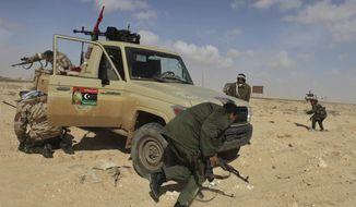 Libyan rebels run for cover after coming under heavy artillery fire from pro-Gadhafi forces along the front line near Brega, Libya, on Friday, April 1, 2011. (AP Photo/Altaf Qadri)