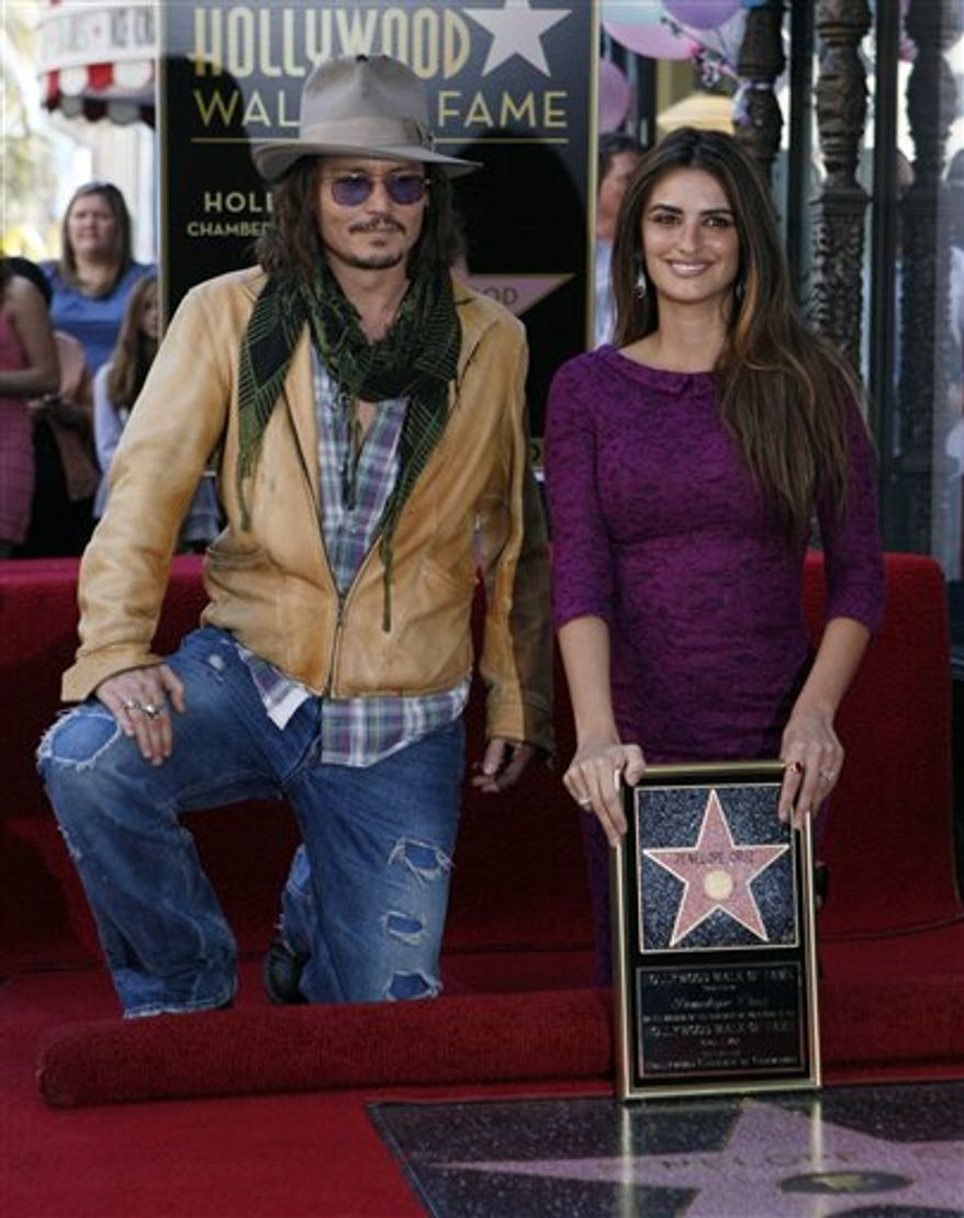 Actor Johnny Depp, left, poses with Spanish actress Penelope Cruz, as she is honored with a star on the Hollywood Walk of Fame on Friday, April 1, 2011 in Los Angeles. (AP Photo/Damian Dovarganes)