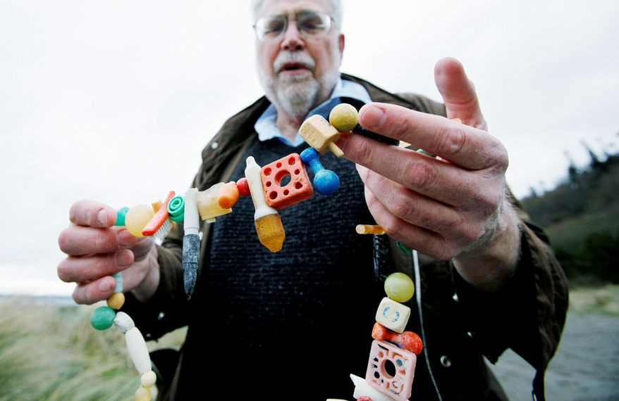 Oceanographer Curt Ebbesmeyer displays a necklace made of ocean flotsam on Wednesday in Seattle. He expects the first items of flotsam from Japan's tsunamis and earthquake to hit West Coast beaches in a year. (Associated Press)