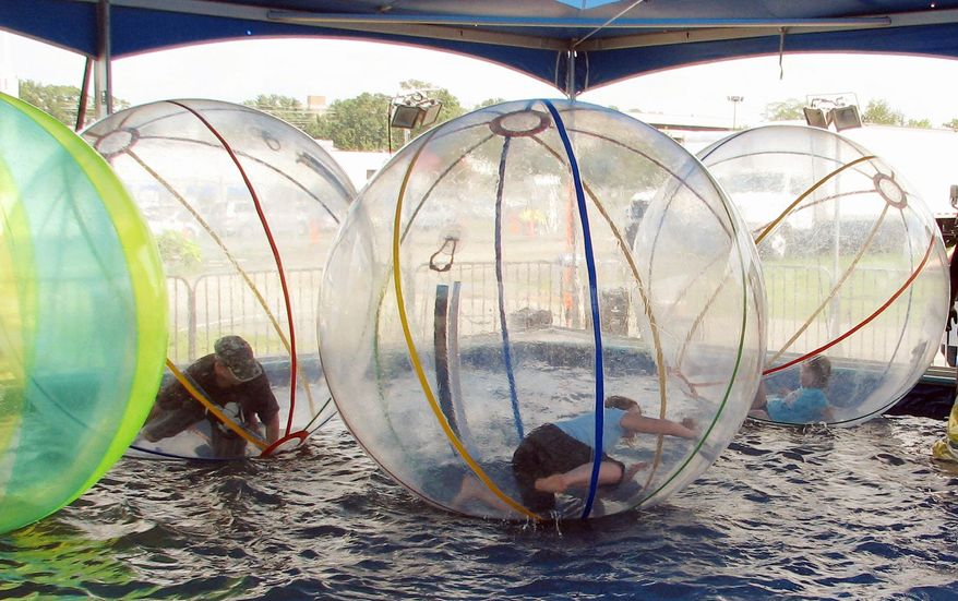 """The Consumer Product Safety Commission cites concern about too little oxygen and carbon dioxide buildup in the inflatable spheres known as """"water walking balls."""" The commission is urging people to stay out of them because of a risk of suffocation or drowning. One company that sells the water balls says on its website that there is enough oxygen to last 30 minutes. (Associated Press/Consumer Product Safety Commission)"""