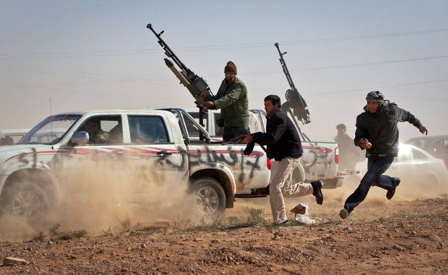 Rebel fighters chase a vehicle belonging to Col. Moammar Gadhafi's forces in a bid to shoot out its tires as it sped through the front line east of Brega on Sunday. The vehicle was driven by a boy who said he had spent two days in besieged Brega and stole the vehicle in order to return to the rebel side. (Associated Press)