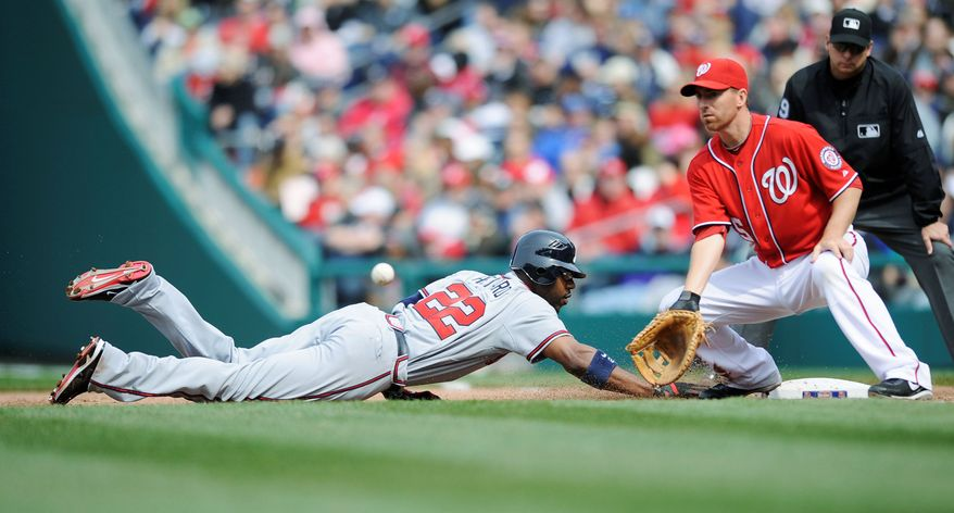 Braves outfielder Jason Heyward (22) slides back to first base safely before the Nationals' Adam LaRoche can apply a tag Sunday. Atlanta capitalized on the Nationals' defensive miscues to win 11-2. (Associated Press)