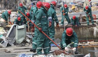 Members of the Japan Maritime Self-Defense Force conduct a search operation for victims of the March 11 earthquake and tsunami in Kamaishi, Iwate Prefecture, Japan, on Saturday, April 2, 2011. (AP Photo/Yomiuri Shimbun, Norimitsu Masuda)