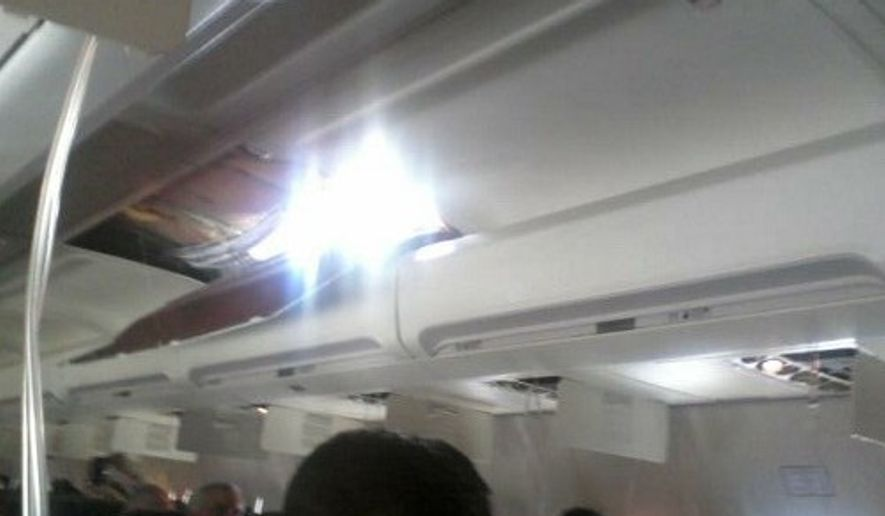 A cellphone photo provided by passenger Joshua Hardwicke shows an apparent hole in the cabin of a Southwest Airlines Boeing 373-300 on Friday, April 1, 2011, as it makes an emergency decent into Yuma, Ariz. (AP Photo/Joshua Hardwicke)