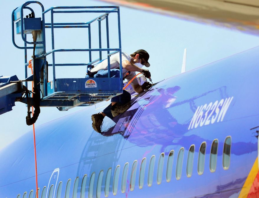 A member of the National Transportation Safety Board investigating the emergency landing of Southwest Airlines Flight 812 cuts away a portion of the plane's fuselage on Sunday in Yuma, Ariz. (AP Photo)