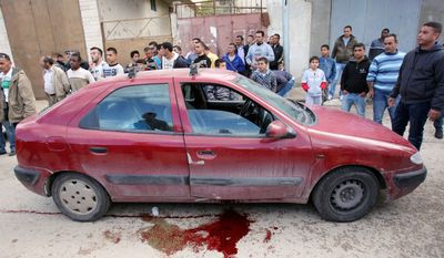 Palestinians gather around the car where Israeli-Arab actor, director and political activist Juliano Mer-Khamis was fatally shot Monday outside his Freedom Theater in the West Bank. (Associated Press)