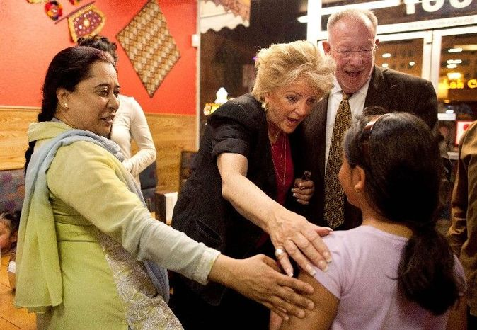 Carolyn Goodman (center) and Las Vegas Mayor Oscar Goodman greet customers at a restaurant while visiting businesses. She is on Tuesday's primary election ballot to succeed him as mayor because of a term-limit law. (Associated Press)