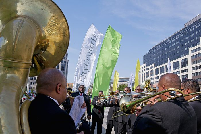 The Sweet Heaven Kings, a trombone shout band from the United House of Prayer for All, play New Orleans-style music as guests leave the groundbreaking for CityCenterDC on Monday after a ceremonial groundbreaking. (Barbara L. Salisbury/The Washington Times)
