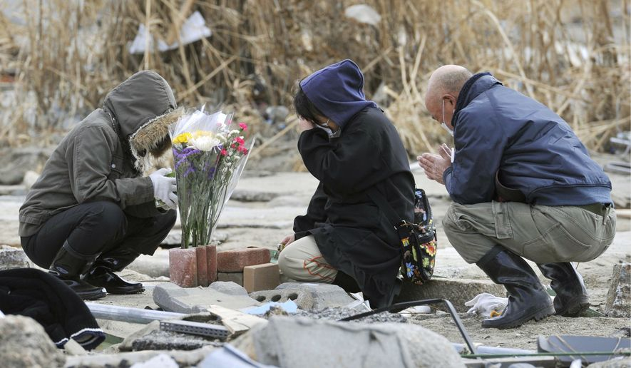 A woman (center) and others pray at her missing parents' house, which was devastated by the March 11 tsunami, in Rikuzentakata, Japan, on Monday, April 4, 2011. (AP Photo/Kyodo News)