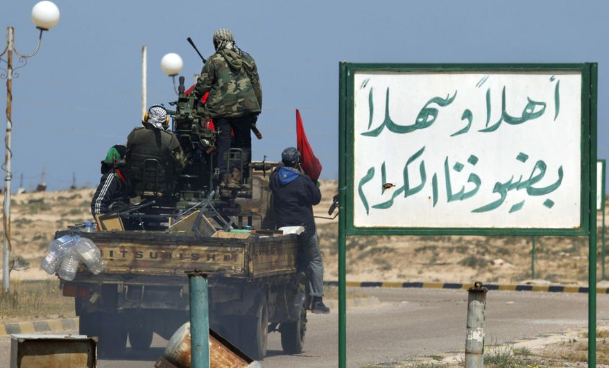 """Libyan rebels on an armed pickup truck drive past an Arabic sign with the words """"You are welcome"""" on their way into the Brega, Libya, during an exchange of fire with pro-Gadhafi forces along the front line at the outskirts of the city on Monday, April 4, 2011. (AP Photo/Nasser Nasser)"""