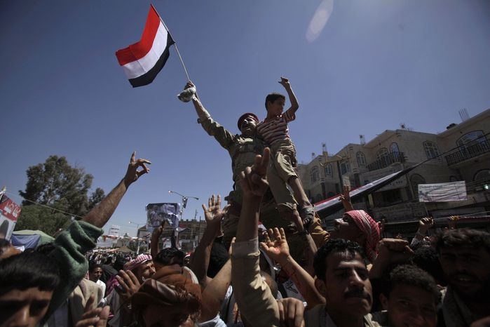 A Yemeni army officer raised aloft by anti-government protesters holds a boy and waves a national flag during a demonstration demanding the resignation of Yemeni President Ali Abdullah Saleh in Sanaa, Yemen, on Monday, April 4, 2011.