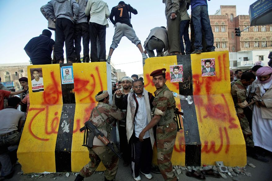 Yemeni army soldiers check anti-government protesters entering the site of a demonstration in Sanaa on Monday. The demonstrators are demanding the resignation of Yemeni President Ali Abdullah Saleh. Yemeni troops opened fire on the crowd. (Associated Press)