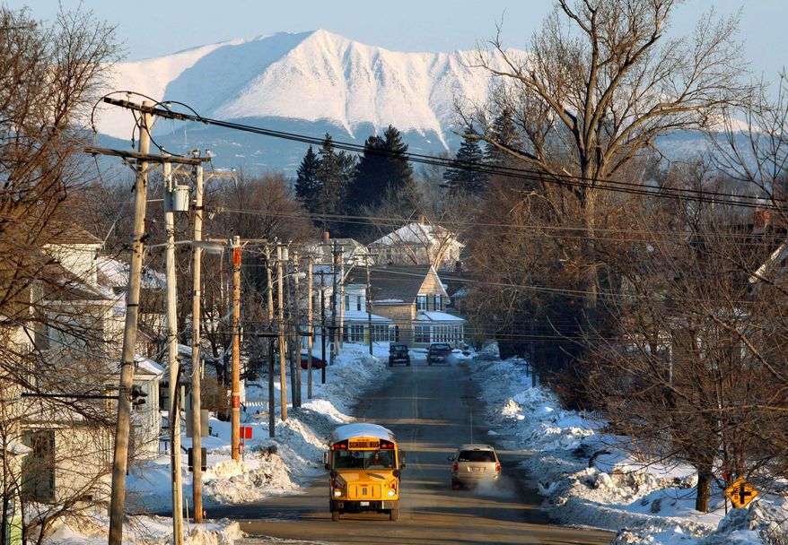 """With Mount Katahdin rising in the background, a school bus makes its rounds in Millinocket, Maine. The state is ranked the """"most peaceful"""" in the nation, according to the first-ever United States Peace Index, a report by the Australia-based Institute of Economics and Peace. (Associated Press)"""
