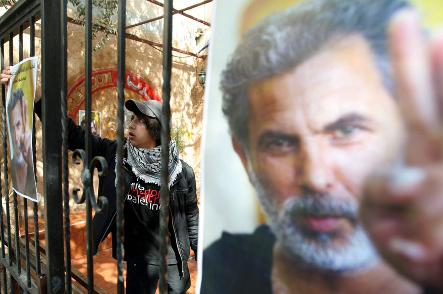 """About 200 Palestinians and foreign activists gathered next to a large picture of slain actor and director Juliano Mer-Khamis flanked by a Palestinian flag and black flag of mourning. """"I promise you to catch whomever did this very soon,"""" his business partner Zakariya Zubeidi told the somber gathering. (Associated Press)"""