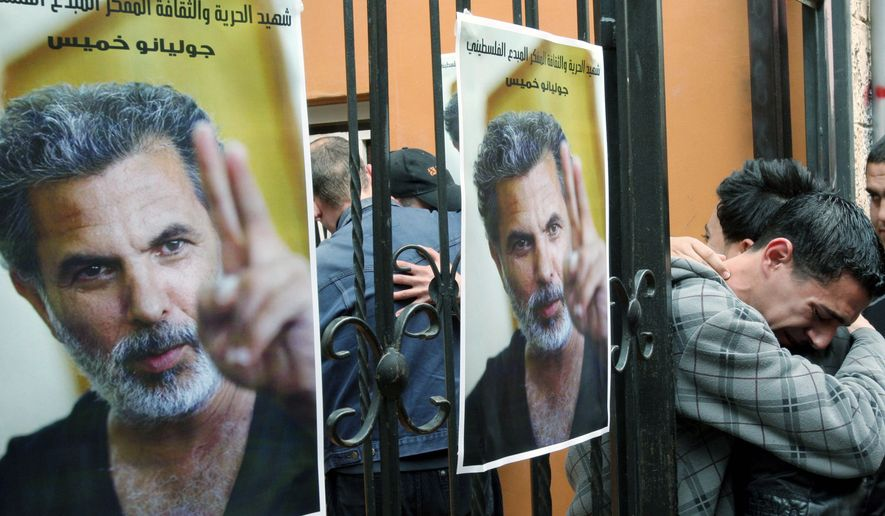 """Palestinian actors mourn the death of actor and director Juliano Mer-Khamis during a vigil in his honor in the West Bank town of Jenin, where he ran a drama school and community theater. Text on the poster reads in Arabic: """"The martyr of freedom and culture, genius Juliano Khamis."""" (Associated Press)"""