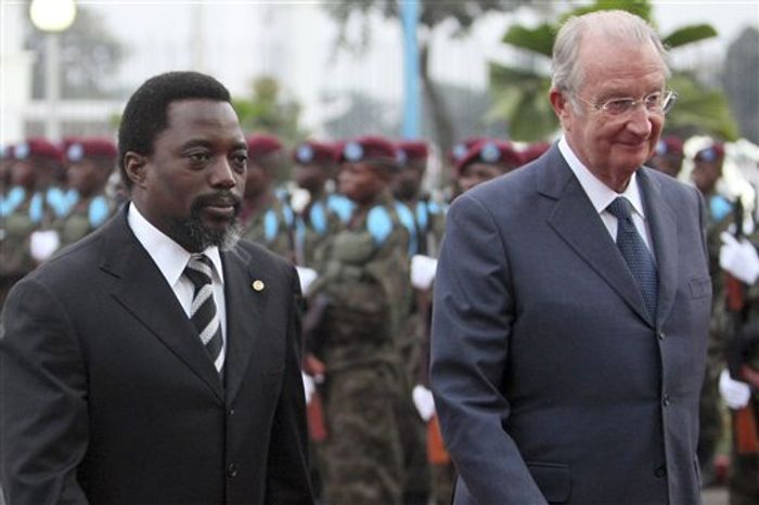 FILE In this June 28, 2010 file photo, Belgium's King Albert II, right, and Congolese President Joseph Kabila, left, participate in a military ceremony upon the King's arrival in Kinshasa, Democratic Republic of Congo. The once-placid Belgian monarchy has turned into a web of intrigue and scandal just as its future is being questioned openly. King Albert II wrath was provoked when Prince Laurent visited Congo, Belgium's former colony, against the wishes of both king and government. (AP Photo/Geert Vanden Wijngaert, file)