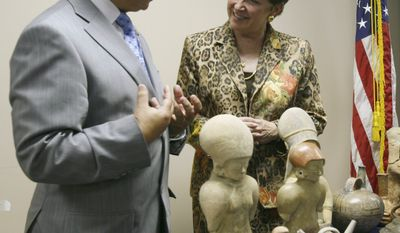 ** FILE ** Heather Hodges, U.S. ambassador to Ecuador, speaks with Juan Carlos Toledo, Ecuadorean consul general in Miami, behind a display of pre-Columbian artifacts at the FBI's Miami field office in North Miami Beach, Fla., in September 2009. (AP Photo/Wilfredo Lee, File)