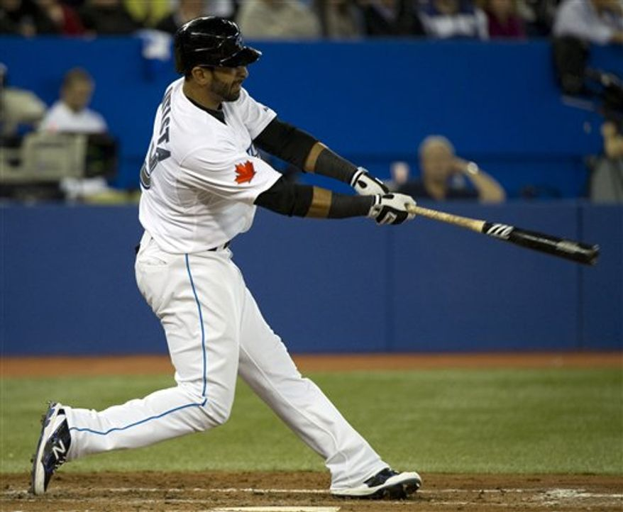 Toronto Blue Jays Jose Bautista makes his first home run swing of the year against Minnesota Twins starter Carl Pavano during fifth-inning AL baseball game action in Toronto on Friday, April 1, 2011.  (AP Photo/The Canadian Press, Nathan Denette)