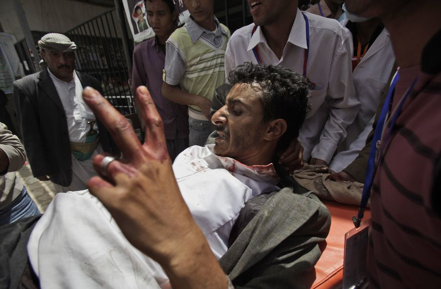 An injured anti-government protestor gestures as he arrives to a field hospital during clashes in Sanaa, Yemen, on Tuesday, April 5, 2011. Opposition parties in Yemen have urged the international community, regional powers and human rights groups to help stop the bloodshed in their country. (AP Photo/Muhammed Muheisen)