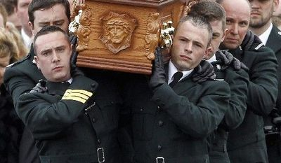 Officers from the Police Service of Northern Ireland officers carry the coffin of slain colleague Constable Ronan Kerr to his funeral Mass in Beragh, Northern Ireland. (Associated Press)
