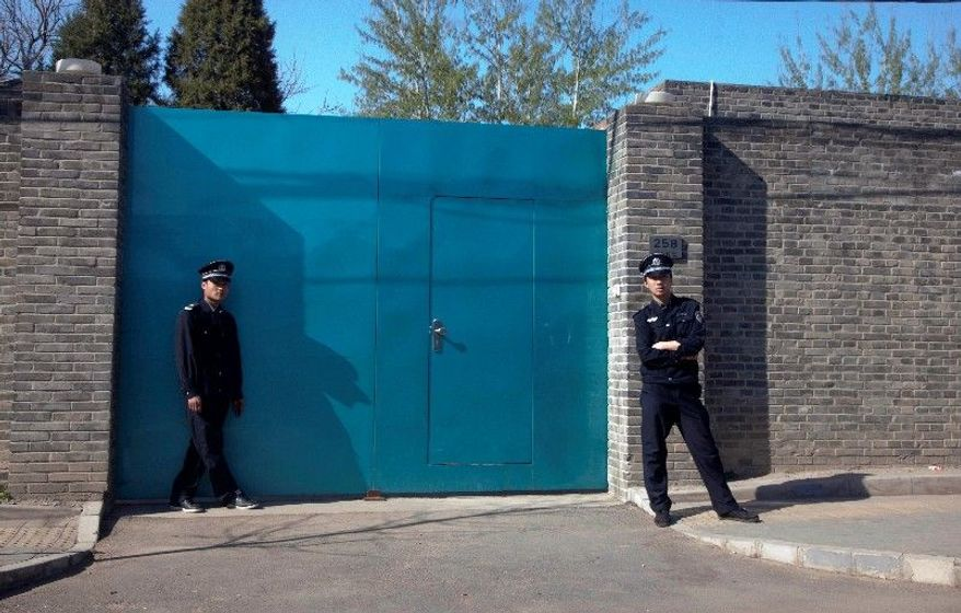 A Chinese police officer (right) and a security guard stand outside the entrance to Ai Weiwei's studio in Beijing. (Associated Press)
