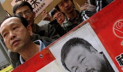 "Human rights protesters carry placards with a picture of Ai Weiwei and the phrase ""Release Ai Weiwei"" outside the China Liaison Office in Hong Kong during a protest on Tuesday. Chinese police have called more people in for questioning as they expand their investigation of the avant-garde artist, who has not been heard from since being taken into custody over the weekend, friends said. (Associated Press)"
