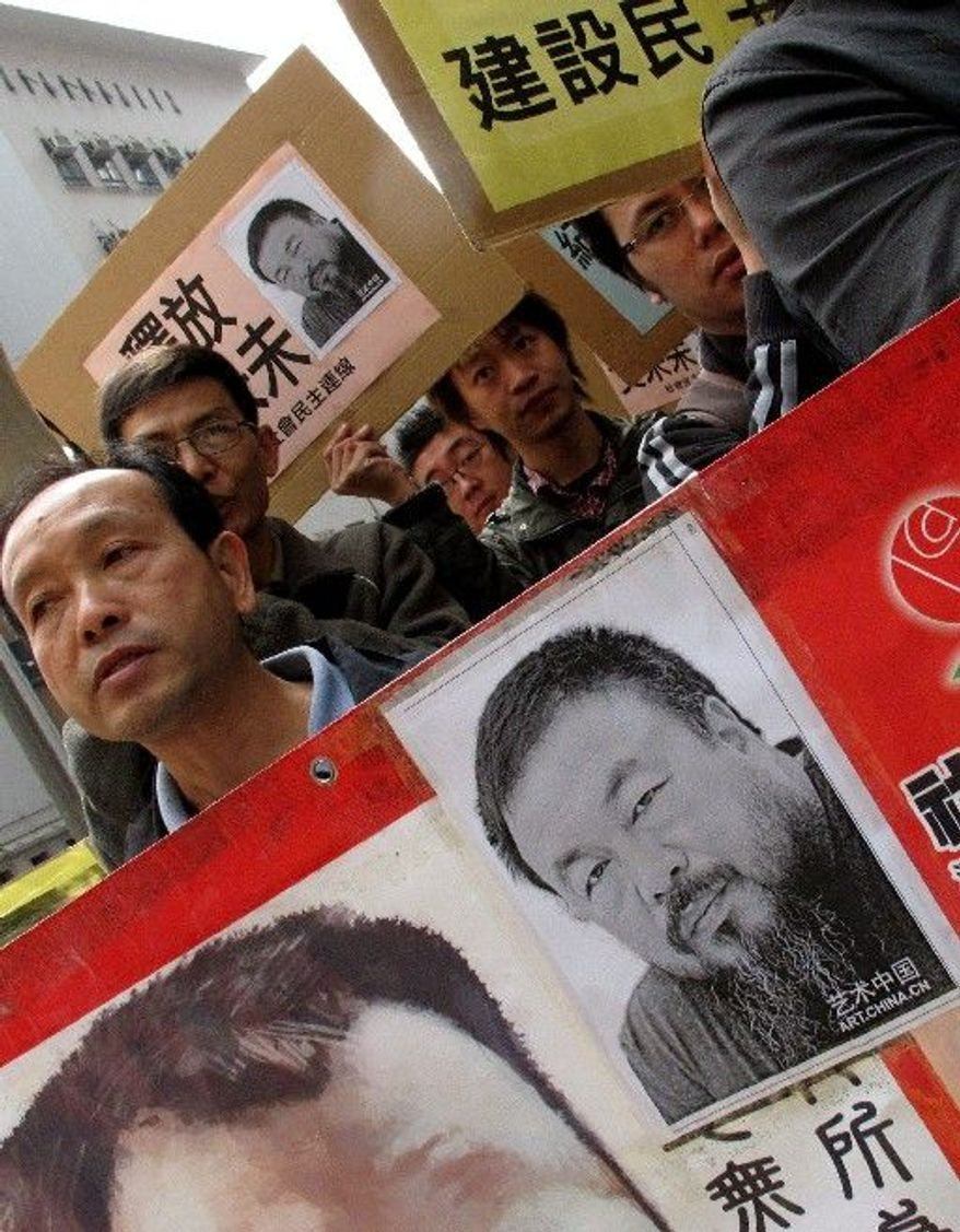 """Human rights protesters carry placards with a picture of Ai Weiwei and the phrase """"Release Ai Weiwei"""" outside the China Liaison Office in Hong Kong during a protest on Tuesday. Chinese police have called more people in for questioning as they expand their investigation of the avant-garde artist, who has not been heard from since being taken into custody over the weekend, friends said. (Associated Press)"""