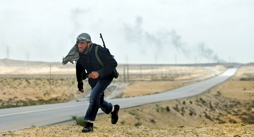 A Libyan rebel runs for safety as shells explode in the distance on the frontline near Brega on Wednesday. Turkey is trying to broker a cease-fire in the fighting with Col. Moammar Gadhafi's forces. The rebels blame the Turks for a lull in the NATO airstrikes that aided their cause. (Associated Press)
