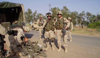 First Lieutenant Ungaro and Second Lieutenant Tilly standby as EOD preps a robot at an IED site in Iraq. (U.S. Army)