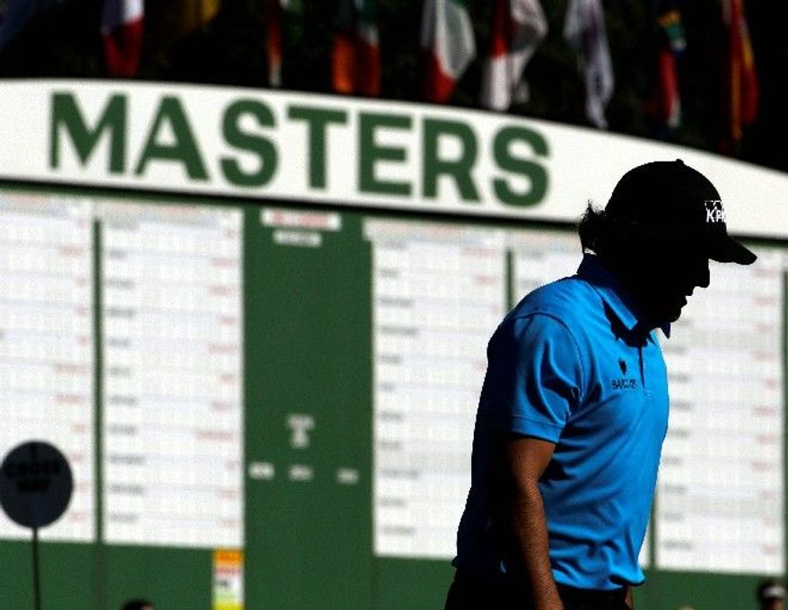 Phil Mickelson (above) walks up to the ninth hole during a practice round for the Masters on Wednesday in Augusta, Ga. Tiger Woods (below) waits to hit off the 13th fairway during his practice round. (Associated Press)