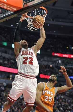 Chicago Bulls' Omer Asik, left, defends against Phoenix Suns' Robin Lopez (15) during the first half of an NBA basketball game Tuesday, April 5, 2011, in Chicago. (AP Photo/Jim Prisching)