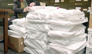 Donna Deuster, assistant city clerk, verifies security tags on sealed bags of 15,600 ballots cast in Racine, Wis. The ballots may have to be recounted in the wake of the narrow margin of victory in the state Supreme Court race. (Associated Press)